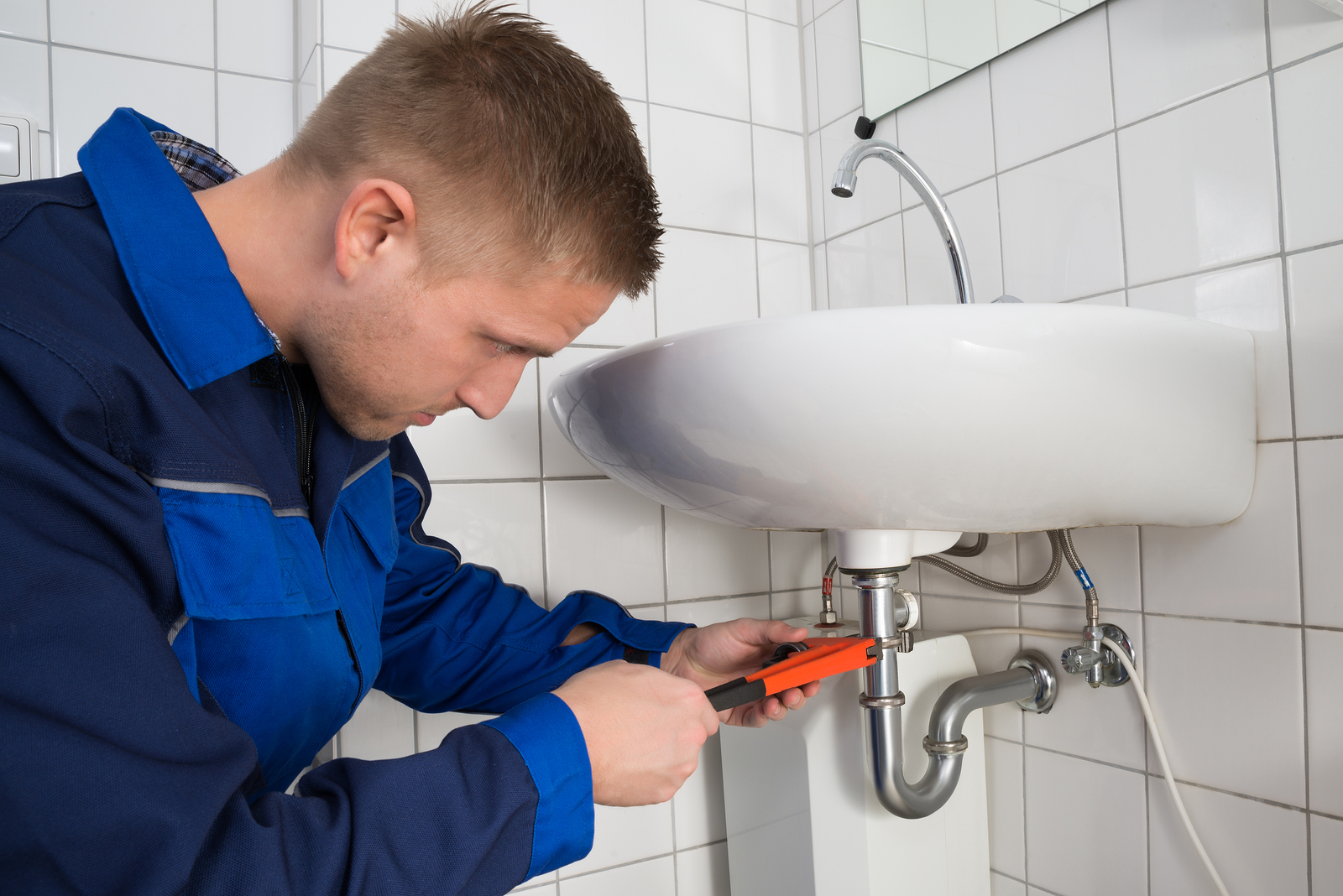 Male Plumber Fixing Sink In Bathroom